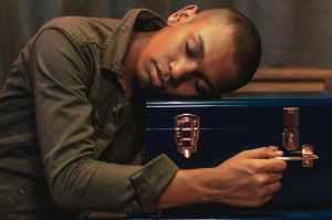 man in green jacket leaning head on blue case